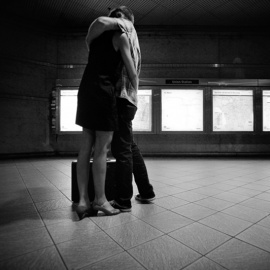 couple-embracing-train-station-76206